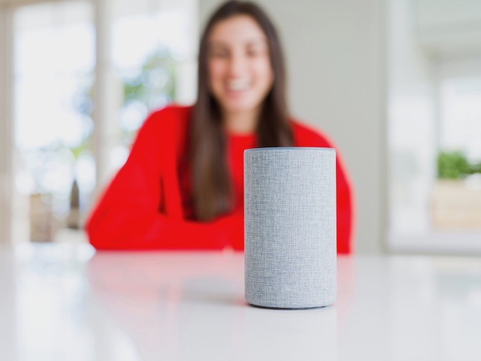 A voice operated smart home device on a table with a woman in the background.